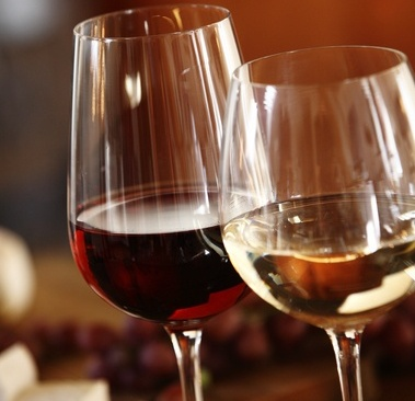 45177451 - elegant glasses of red and white wine served together on a dining table for a formal meal, close up of the bowls of the wineglasses and the wine